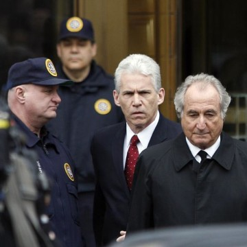 "Bernard Madoff, right, exits the Manhattan federal courthouse in New York in this March 10, 2009, file photo. Madoff says through his efforts, victims could be repaid all their original principal. He also claims he has information that ""would clearly demonstrate the vital role the major banks … played in the carrying out [of] my fraud."""