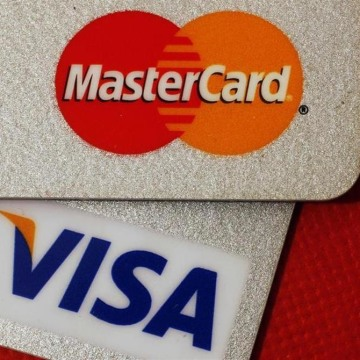 A judge approved a class-action settlement between merchants and MasterCard and VISA over transaction fees. But some merchants dropped out of the case in opposition.