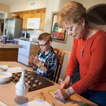 Leslie Davis helps her grandchildren bake holiday cookies on Saturday at her home in Mesa, Ariz.