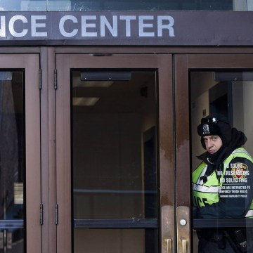 A police officer looks out of an entrance to the Science Center at Harvard University in Cambridge, Massachusetts, December 16, 2013. Harvard Universi...