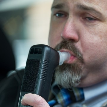 "Bill Chastain, state director with LifeSafer, demonstrates a breath alcohol ignition interlock device during a ""Drive Sober or Get Pulled Over"" news conference Dec. 17 in Washington, D.C. The National Highway Traffic Safety Administration director wants all states to require the devices for first-time offenders."