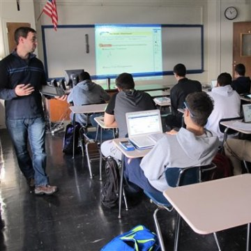 In this Dec. 13, 2013 photo, math teacher Richard Yapchanyk, left, leads a math class at Archbishop Stepinac High School as students use tablets and l...
