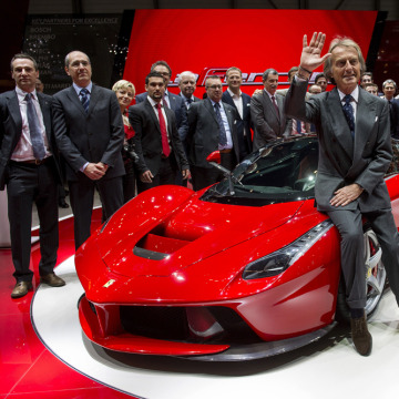 Ferrari President Luca Cordero di Montezemolo (C) waves to media after the World premiere presentation of the new La Ferrari hybrid model car at the I...