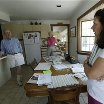 Robert Post, left, and his wife, Jane Post, center, talk to neighbor Gail Kender inside their home, in Mantoloking, N.J. The Posts' home was flooded during Superstorm Sandy, wiping out the phone line. Post has a pacemaker that needs to be checked once a month by phone, but the phone company refuses to restore the area's landlines after they were damaged by the storm.