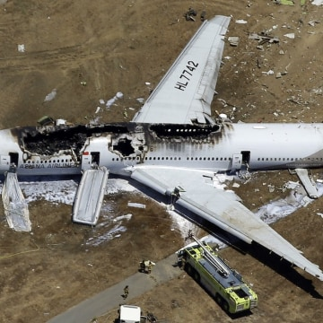 In this Saturday, July 6, 2013 aerial photo, the wreckage of Asiana Flight 214 lies on the ground after it crashed at the San Francisco International ...