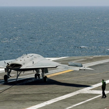 An X-47B pilot-less drone combat aircraft comes to a stop after landing on the deck of the USS George H.W. Bush aircraft carrier in the Atlantic Ocean...