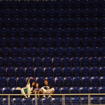 FILE--MIAMI, FL - APRIL 13:  A family sits in an empty section of seats during the Miami Marlins and Philadelphia Phillies game at Marlins Park on Apr...