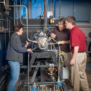 Task lead Tyler Hickman, in red shirt, and technicians inspect the 3D-printed rocket injector assembly as it's installed in the Rocket Combustion Laboratory at NASA's Glenn Research Center.