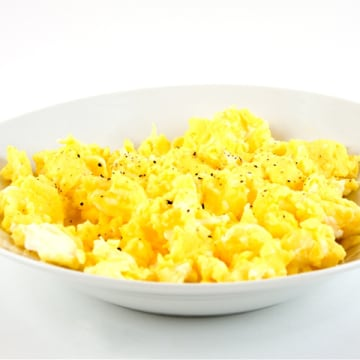 A bowl of scrambled eggs with cracked pepper