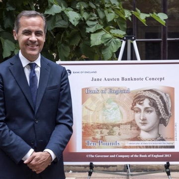Bank of England Governor Mark Carney poses next to a new British ten pound Sterling banknote bearing the likeness of author Jane Austen in a picture r...