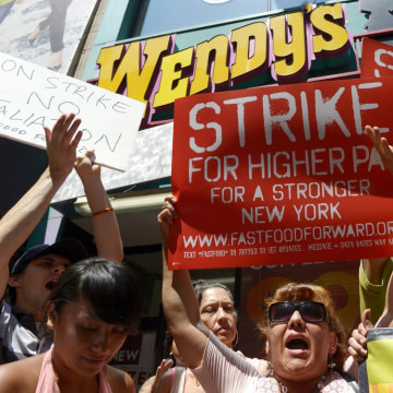epa03806747 People gather outside of a Wendy's restaurant as part of a one day strike calling for higher wages for fast food workers in New York, New ...