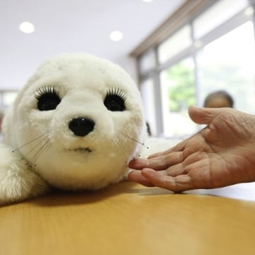 In this combination picture, a  therapeutic robot named Paro opens its eyes as it reacts to an elderly user's hand at the Suisyoen retirement home, ab...