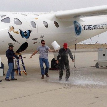 New Virgin Galactic pilot C.J. Sturckow, a four-time space shuttle astronaut, gets a traditional dousing after flying the company's WhiteKnightTwo mot...