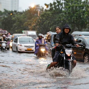 Motorists maneuver through floodwaters following monsoon rains