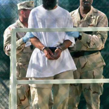 **  FILE ** In this April 5, 2006 file photo, reviewed by U.S. military officials, military personnel transport a detainee into a building within the ...