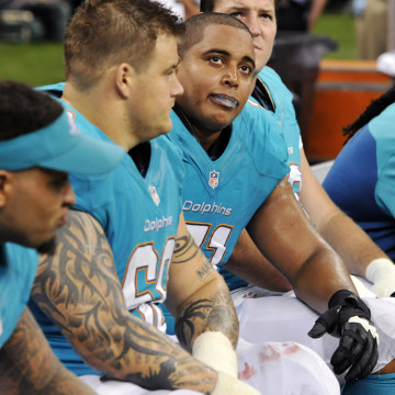 Miami Dolphins guard Richie Incognito (68) and tackle Jonathan Martin (71) look up from the bench in the second half of an NFL football game against t...