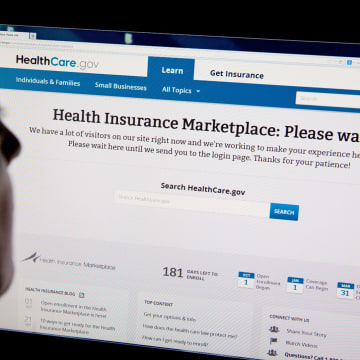 "A woman looks at the HealthCare.gov insurance exchange internet site showing a ""Please wait"" page"