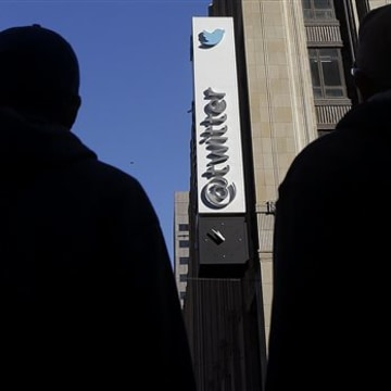 Pedestrians cross the street in front of Twitter headquarters in San Francisco. As it nears its IPO, the company is building the foundation for new revenue streams.