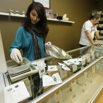 Monique Rydberg, left, weighs and packages medical marijuana, as Jeff Clark, right, awaits patients at the cash register, Wednesday, Oct. 16, 2013, at The Joint, a medical marijuana cooperative in Seattle. Marijuana businesses are drawing the eye of investors, who see it as a growth industry.