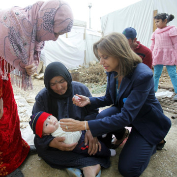 Annamaria Laurini, UNICEF Representative in Lebanon, administers a polio vaccine to a baby on Nov. 8, 2013, at a Syrian refugee camp near Zahle town in the Bekaa Valley in Lebanon.