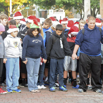 Members of the Port Clinton, Ohio, community pause for a moment of silence on Oct. 28, 2013, during a ceremony for Devin Kohlman outside his home.