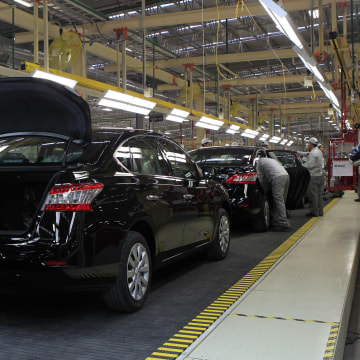 Employees work at a production line before the opening of Nissan's new plant in Aguascalientes, Mexico, on Nov. 12, 2013. Nissan Motor Co. will be producing 1 million cars in Mexico by 2016.
