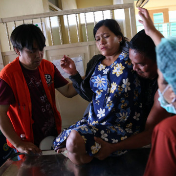 A pregnant woman is helped onto a trolley in a Tacloban hospital on Friday in the Philippines.