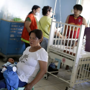 Christine Badanoy, 37, holds her a week-old baby girl, Ujan Marvie, in a medical center in Tacloban, Philippines.
