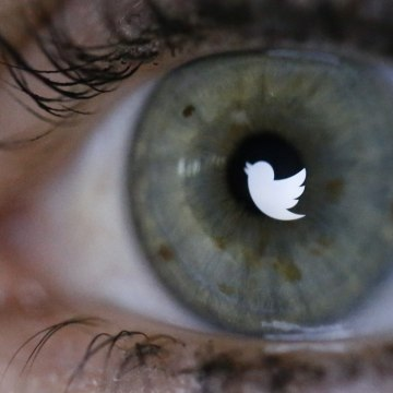 IMAGE: Twitter logo reflected in the eye of a woman in Berlin.