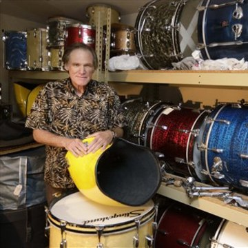 James Glay poses with his collection of vintage drums in Arlington Heights, Ill. He's among the older Americans fueling a wave of entrepreneurship.