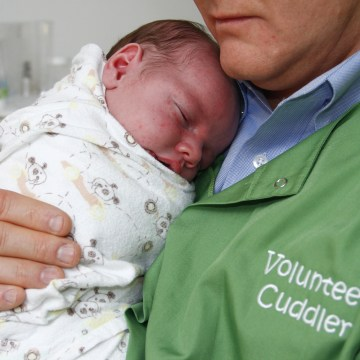 Baby Jason, 3 ½ weeks, is held snugly by Chuck Morgan, a volunteer                    'cuddler' with East Tennessee Children's Hospital.