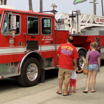 VENICE, CA - JULY 6:  A family watches a firetruck pass a business on the boardwalk that certifies people to smoke medical marijuana with $40 evaluati...