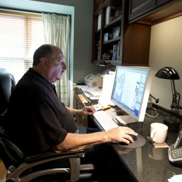 In this Wednesday, Oct. 9, 2013 photo, graphic designer Tom Sadowski, 65, who delayed his retirement, works from home in Sterling, Va.