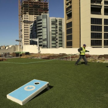 A worker tends to the lawn on the roof of Twitter headquarters in San Francisco in this Oct. 4 photo. As Twitter prepares for its IPO, some investors are nervous about its outlook.