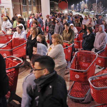 Shoppers wait outside the Target store in Lisbon, Conn., before the store opens for Black Friday in this 2011 file photo. The end of the government shutdown could mean more deals for consumers.