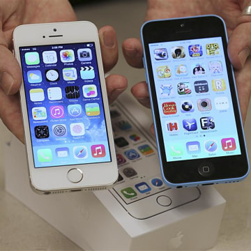 An employee shows the the front of a new Apple iPhone 5C (R) and iPhone 5 S (L) at a Verizon store in Orem, Utah September 19, 2013. REUTERS/George Fr...