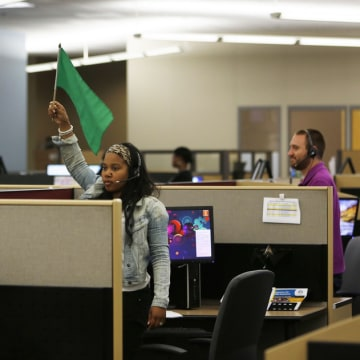 A customer service agent at Covered California's Concord call center waves a flag for technical assistance during the opening day of enrollment of the...