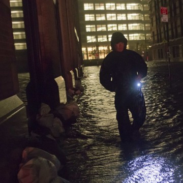 A security guard walks through a flooded street in the financial district of Manhattan, New York, on Oct. 30, 2012.
