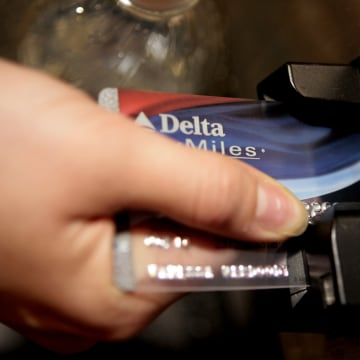 FILE - In this Dec. 14, 2007 file photo, a traveler uses a Delta SkyMiles credit card to buy an airline e-ticket at the Bob Hope Airport in Burbank, C...