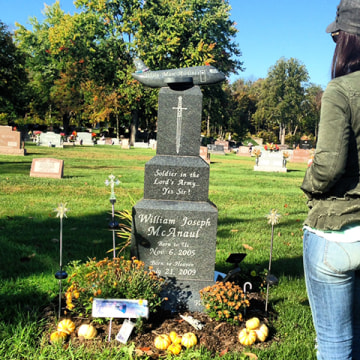 A woman visits the grave of Will McAnaul, a 4-year-old boy who died after a gun incident in 2009.