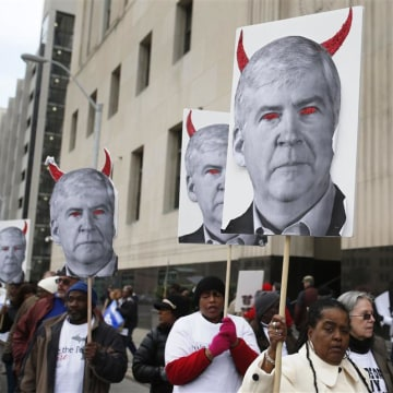 Protesters hold posters depicting Michigan Gov. Rick Snyder as a devil, at a rally outside Theodore Levin U.S. Courthouse during Detroit's bankruptcy eligibility trial in Detroit on Monday.