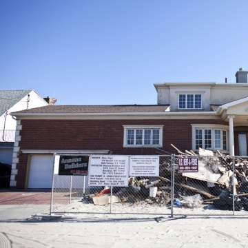 A year later, a house damaged by Superstorm Sandy stands protected by a fence in the Belle Harbor section in the Queens borough of New York City. Hundreds of buildings are still affected, and some people are dealing with health problems because of mold.