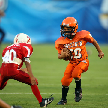 Members of Pop Warner youth football teams compete in an exhibition match at halftime of the San Diego Chargers NFL preseason football game against th...