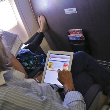 Passenger uses tablet.