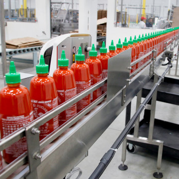 This Tuesday Oct. 29, 2013 photo shows Sriracha chili sauce moves along a production line during at the Huy Fong Foods factory in Irwindale, Calif., o...