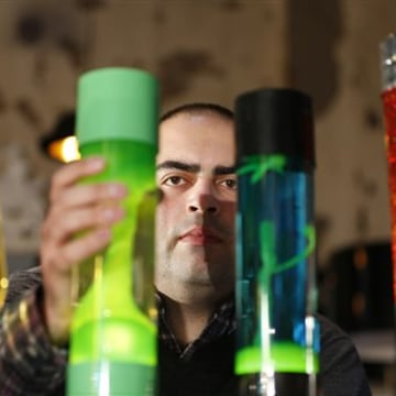 In this Monday, Aug. 19, 2013, Anthony Voss, lava lamp expert and collector, poses for the photographer in a shop in London with some of the lava lamp...