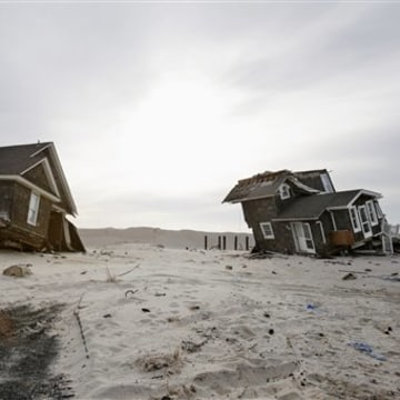 FILE - This Feb. 22,2013 file photo shows Two heavily damaged homes on the beach in Mantoloking, N.J., from Superstorm Sandy. Man-made global warming ...