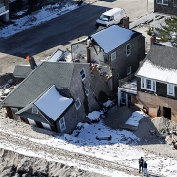 FILE - In this Nov. 9, 2012 aerial-file photo, people stand near damaged homes along the Atlantic Ocean in New Jersey after the region was pounded by ...