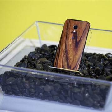 A phone with a wooden back on it rests in a display at a launch event for Motorola's new Moto X phone in New York, in this August 1, 2013, file photo....