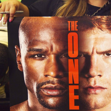 "A fan holds a poster as she waits for boxers Floyd ""Money"" Mayweather Jr. and Saul ""Canelo"" Alvarez to arrive at the MGM Grand Hotel and Casino in Las..."
